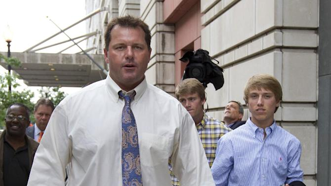 Former Major League Baseball pitcher Roger Clemens, left, gestures as he leaves Federal Court in Washington with sons, Kacy, center back, and Kody, right, Tuesday, June 12, 2012. Clemens' fate is in the hands of a jury that will decide if the former pitcher lied about performance-enhancing substances. The panel of eight women and four men began deliberations after a day of closing arguments in the ninth week of the trial.  (AP Photo/Manuel Balce Ceneta)