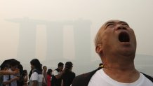 A tourist poses for photos with the Merlion in the hazy skyline of Singapore