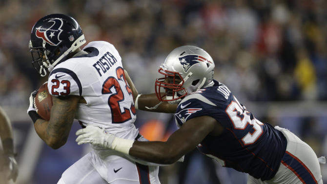 New England Patriots defensive end Chandler Jones, right, tries to tackle Houston Texans running back Arian Foster during the first half of an AFC divisional playoff NFL football game in Foxborough, Mass., Sunday, Jan. 13, 2013. (AP Photo/Elise Amendola)