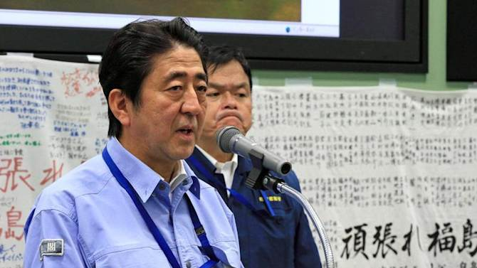 Japan's PM Abe speaks to workers during his inspection tour to TEPCO's tsunami-crippled Fukushima Daiichi nuclear power plant in Okuma
