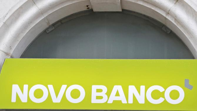 A woman walks past a sign for Portuguese Novo Banco (New Bank) in Lisbon