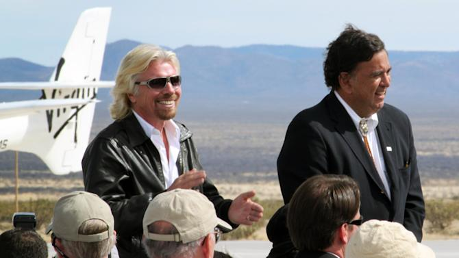 In this Oct. 22, 2010, image, Virgin Galactic founder Richard Branson, left, claps during a runway dedication ceremony at Spaceport America in Upham, N.M. Branson has vowed to be one of the first passengers when Virgin Galactic begins commercial space tourism flights from the spaceport. (AP Photo/Susan Montoya Bryan)