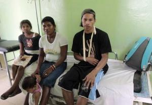 Enrique Simons, one of the twenty miners rescued from a gold mine after a landslide, sits on a bed at a hospital in Bonanza town