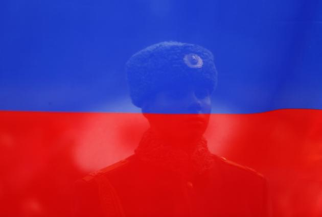 Russian soldier looks at a Russian flag during a medal ceremony at the 2014 Sochi Paralympic Winter Games in Rosa Khutor