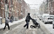 A woman crosses a snow-covered street with a pushchair in Armentieres, northern France, on March 5. An increase in energy imports due to a cold snap in February sent France&#39;s trade deficit jumping by nearly 15 percent in February to hit 6.4 billion euros ($8.4 billion), customs data showed Friday