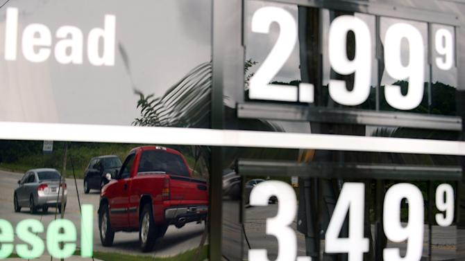 In this Monday, July 1, 2013, photo, vehicles are reflected in a sign advertising unleaded gas for $2.99 at a QuikTrip station at the corner of Woodruff Rd. and Verdae Blvd. in Greenville, S.C. The government reports on consumer prices for July on Thursday, Aug. 15, 2013. (AP Photo/Rainier Ehrhardt)