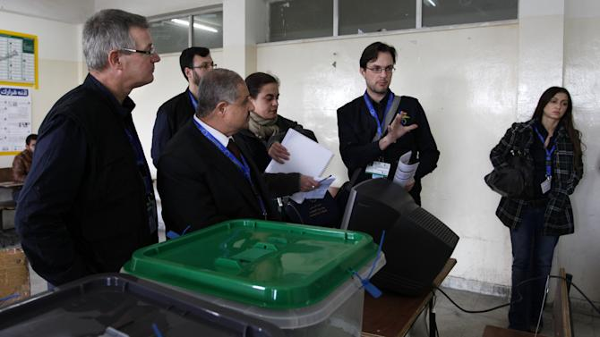 Chief observer of the European Union election, David Martin, left, and his crew speak to members of the Jordanian Independent Electoral Commission, in Amman, Jordan, Wednesday Jan. 23, 2013. Martin, said voting got off to a relatively smooth start, with only one or two insignificant violations of rules due to campaigning outside polling stations. EU observers are stationed in all of Jordan's 12 governates, he said. (AP Photo/Mohammad Hannon)