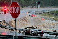 Floodwaters race across the Oxenford - Tamborine road on Australia&#39;s Gold Coast on January 28, 2013. Helicopters have plucked dozens of stranded Australians to safety in dramatic rooftop rescues as severe floods swept the northeast, killing four people and inundating thousands of homes