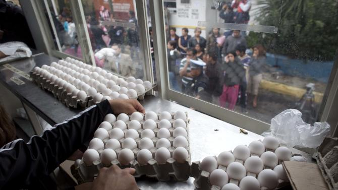 A city worker sells eggs at government subsidized prices as people line up outside the city truck in Mexico City, Friday, Aug. 24, 2012. The Mexican government is battling an egg shortage and hoarding that have caused prices to spike in a country with the highest per-capita egg consumption on earth.  About 11 million chickens were slaughtered after a June outbreak of bird flu. (AP Photo/Alexandre Meneghini)