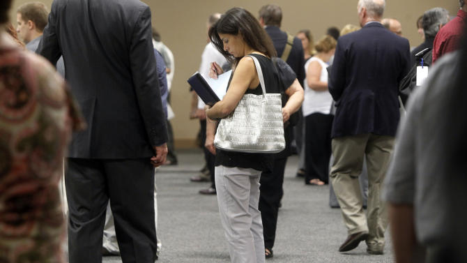 FILE - In this Monday, July 15, 2013 file photo, a woman waits to talk with employers at a job fair for laid-off IBM workers in South Burlington, Vt. The government issues the jobs report for July on Friday, Aug. 2, 2013. (AP Photo/Toby Talbot, File)