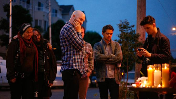 In this Wednesday, May 30, 2012 photo, people grieve for victims outside Cafe Racer in Seattle, where a gunman killed four people earlier in the day. The gunman then killed a fifth person in a carjacking before he apparently shot himself as officers closed in following a citywide manhunt. (AP Photo/seattlepi.com, Sofia Jaramillo)  MAGS OUT; NO SALES; SEATTLE TIMES OUT; TV OUT; MANDATORY CREDIT