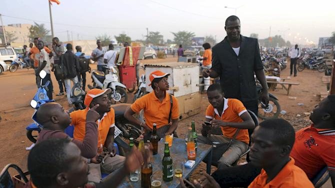 Supporters of Burkina Faso's President-elect Roch Marc Kabore have a drink outside Kabore's campaign headquarters in Ouagadougou