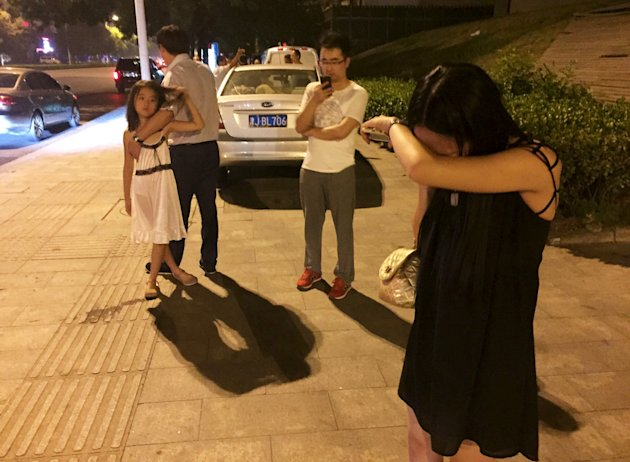People react near a street after a blast at Binhai new district, in Tianjin municipality, China, August 12, 2015. A huge explosion hit an industrial a...