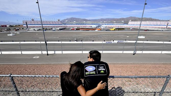 IndyCar race fans Donna and Chris Martinez pay their respects to driver Dan Wheldon at the Las Vegas Motor Speedway in Las Vegas, Monday, Oct. 17, 2011, where Wheldon died Sunday after a massive, fiery wreck during the Las Vegas Indy 300. (AP Photo/Chris Carlson)
