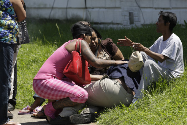 A woman is overcome with grief at the scene where four people were shot on a street corner in a west Louisville neighborhood Thursday, May 17, 2012. Police say two of the four people have died after being shot near 32nd and Kentucky Streets, and more gunfire rang out while officers were investigating. (AP Photo/The Courier-Journal, Michael Clevenger) NO SALES; MAGS OUT; NO ARCHIVE; MANDATORY CREDIT