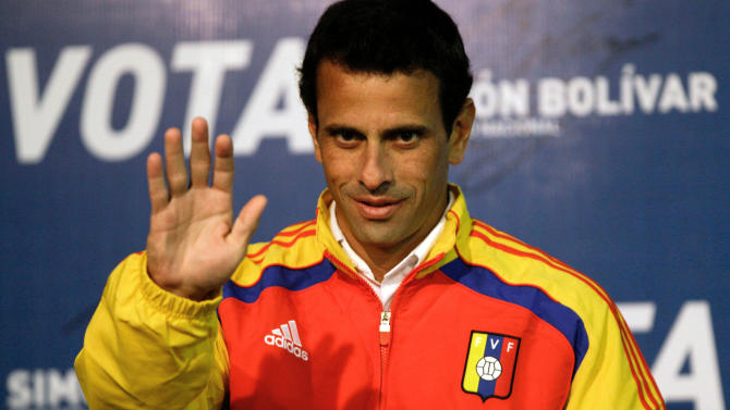 Opposition presidential candidate Henrique Capriles waves as he arrives to a news conference in Caracas, Venezuela, Saturday, April 13, 2013. Capriles is running against ruling party candidate and acting President Nicolas Maduro in Sunday's special presidential election. (AP Photo/Fernando Llano)