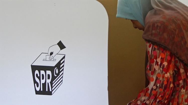 A Malaysian voter casts her ballot in the general elections at a polling station in Pekan, Pahang state, Malaysia, Sunday, May 5, 2013. Malaysians have begun voting in emotionally charged national elections that could see the long-ruling coalition ousted after nearly 56 years in power. (AP Photo/Lai Seng Sin)