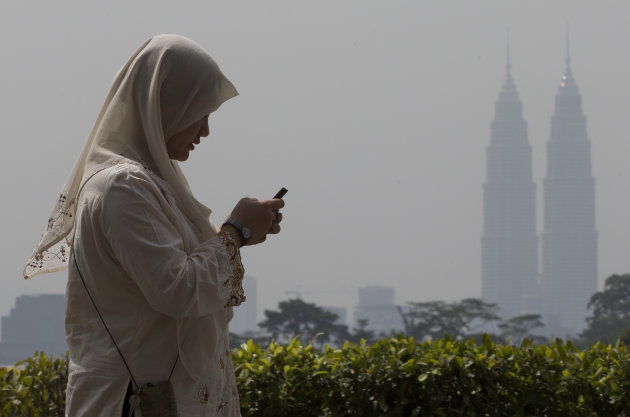 A woman checks her mobile phone as she walks past Malaysia's landmark Petronas Twin Towers in Kuala Lumpur, Malaysia, Thursday, June 20, 2013. Smoke haze is a nearly annual problem for Singapore and i