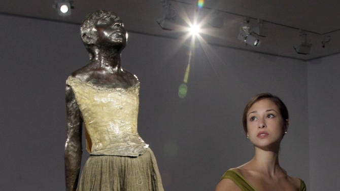 """FILE - In a Tuesday, Oct. 25, 2011 file photo, Puanani Brown, a member of the corps de ballet of the American Ballet Theatre, poses with Edgar Degas """"Petite danseuse de quatorze ans,"""" at Christie's auction house, in New York.  The bronze sculpture failed to find a buyer at Christie's New York auction of impressionist and modern art Tuesday night, Nov. 1, 2011. The sculpture had a pre-sale estimate of $25 million to $35 million, but there were no bids.  (AP Photo/Richard Drew, File)"""