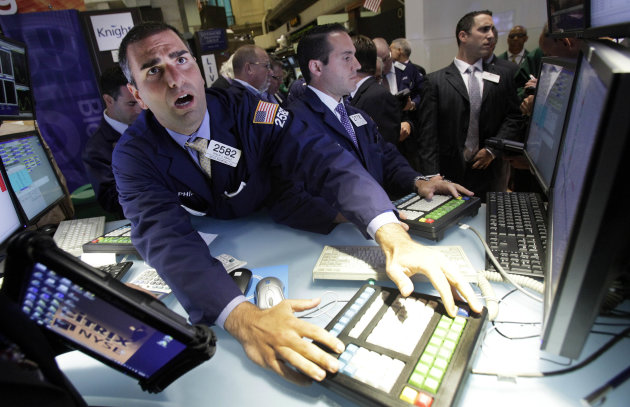 Specialist Philip Finale, left, works at his post on the floor of the New York Stock Exchange Thursday, July 26, 2012. U.S. stocks soared at the opening bell after the president of the European Central Bank vowed to do what it takes to preserve the continent's monetary union. (AP Photo/Richard Drew)