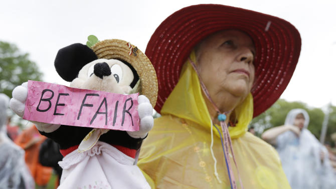 Demonstrator Carole Fields, of Palm Beach, Fla., listens to a speech, Monday, Aug. 27, 2012, in Tampa. Hundreds of protestors gathered in a park in Tampa to march in demonstration against the Republican National Convention. (AP Photo/Chris O'Meara)