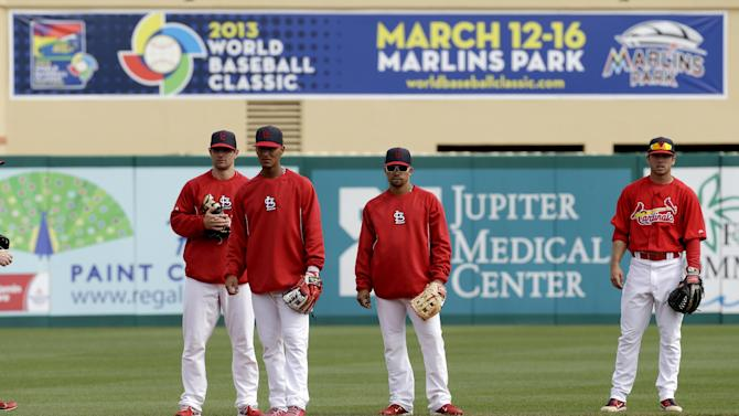 St. Louis Cardinals shortstop Rafael Furcal, center right, looks on as short stops, from left, Pete Kozma, Ronny Cedeno and Greg Garcia field ground balls before an exhibition spring training baseball game against the Washington Nationals, Saturday, March 2, 2013, in Jupiter, Fla. Furcal was scratched from the line up for Saturday's game. (AP Photo/Julio Cortez)