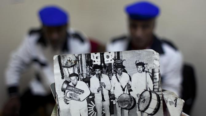 """In this Thursday, Jan. 10, 2013 photo, Egyptian musician and drum player Ezzat el-Fayoumi, 65, the last member of one of Egypt's oldest and best known percussion music bands, called Hassaballah, holds a photo of the original band with him in it, at right, among his late team mates while performing at a theater in 1975, in Cairo, Egypt. During its heyday,  Mohammed Ali street was famed as the lively and romantic heart of Arabic music and home to musicians, belly-dancers and instrument makers. """"The street is extinct,"""" el-Fayoumi said, sitting at a coffee shop that now serves as his office. """"When I die, there will be no more music. No one is learning it."""" (AP Photo/Nasser Nasser)"""