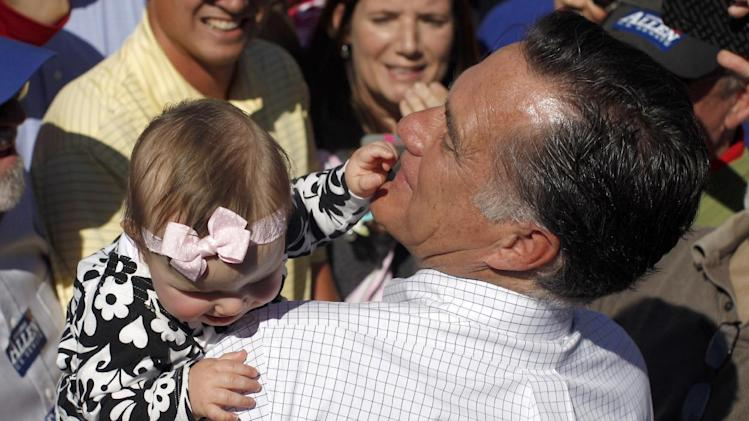 Republican presidential candidate, former Massachusetts Gov. Mitt Romney picks up a baby as he campaigns at the Mobility Supercenter in Richmond, Va., Friday, Oct. 12, 2012. (AP Photo/Charles Dharapak)