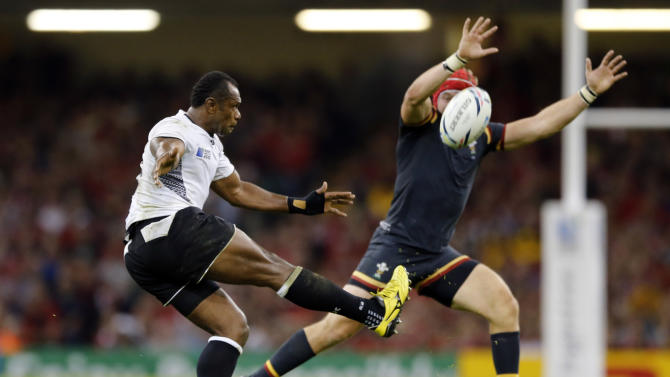 Fiji's Lepani Botia kicks the ball past Wales' Tyler Morgan during the Rugby World Cup Pool A match between Wales and Fiji at the Millennium Stadium, Cardiff, Thursday, Oct. 1, 2015. (AP Photo/Frank Augstein)