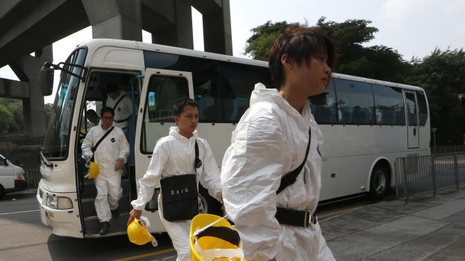 Search and rescue workers arrive at a public mortuary in Hong Kong Tuesday, Oct. 2, 2012. A boat packed with revelers on a long holiday weekend collided with a ferry and sank off Hong Kong, killing at least 36 people and injuring dozens, authorities said. The two vessels collided Monday night near Lamma Island off the southwestern coast of Hong Kong Island. (AP Photo/Kin Cheung)