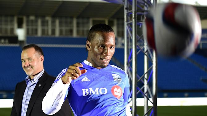 Ivorian striker Didier Drogba kicks the ball in front of Montreal Impact president Joey Saputo after a press conference on July 29, 2015 in Montreal