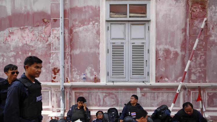 Policemen rest inside the compound of the Government House, as anti-government protesters gather behind its fence and gates in Bangkok