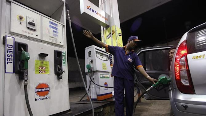 A worker fills a car with petrol as he gestures towards the fuel barometer for the passenger to check, at a fuel station in Kolkata