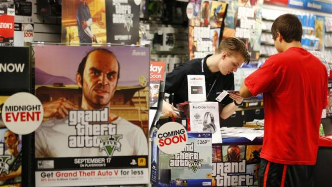 """Game enthusiasts purchase the latest release of """"Grand Theft Auto Five"""" after the game went on sale at the Game Stop store in Encinitas, California"""