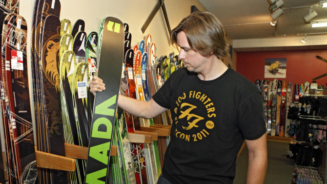 In this Sept. 21, 2012 photo, Rich Maloy looks at skis at a ski shop in Boulder, Colo. Maloy of Boulder didn't buy a season pass after moving to Colorado from New York last year, partly due to poor snow. But this year, he bought an Epic Local pass from Vail Resorts for access, with some restrictions, to the company's seven resorts plus Arapahoe Basin, along with a four-pack, good for four days at Loveland. (AP Photo/Ed Andrieski)