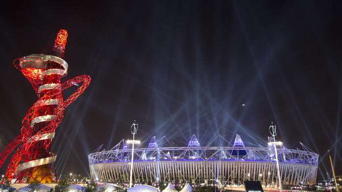Searchlights shine over the Olympic Stadium during a rehearsal for the opening ceremony at the 2012 Summer Olympics, Wednesday, July 25, 2012, in London. The city will host the 2012 London Olympics with opening ceremonies for the games scheduled for Friday, July 27. (AP Photo/Ben Curtis)