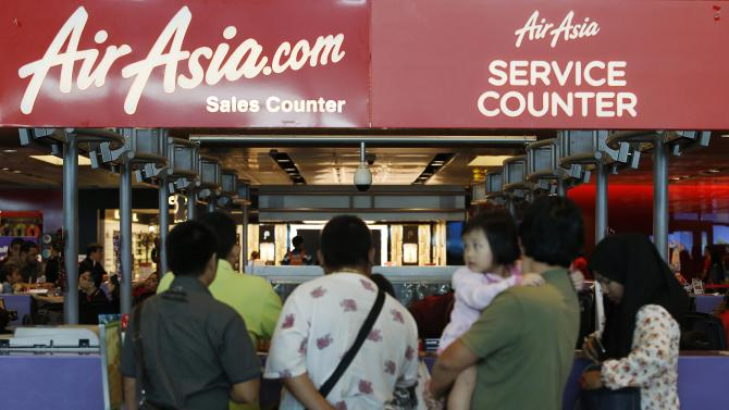People queue at an AirAsia counter at Changi Airport in Singapore
