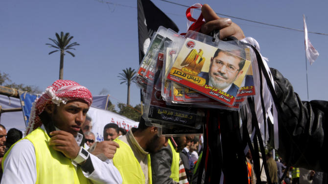"""An Egyptian vendor displays plastic cards with the picture of Islamist President Mohammed Morsi, during a rally outside Cairo University in Cairo, Egypt, Friday, Feb. 15, 2013. Around 5,000 mostly hardline Islamists are rallying in Egypt against a recent wave of protests that has killed around 70 people. Arabic reads """"Mohammed Morsi president of all Egyptians."""" (AP Photo/Amr Nabil)"""