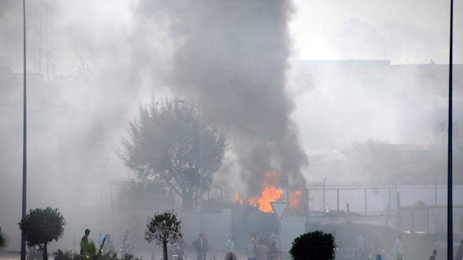The American school adjacent to the U.S. embassy compound burns during clashes in Tunis, Tunisia, Friday, Sept. 14, 2012. Thousands of demonstrators massed outside the embassy and several were seen climbing the outer wall of the embassy grounds, an Associated Press reporter on the scene said. (AP Photo/Hassene Dridi)