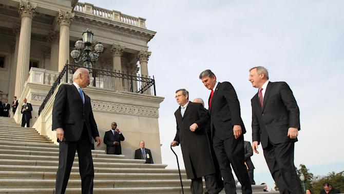 IMAGE DISTRIBUTED FOR REHABILITATION INSTITUTE OF CHICAGO - U.S. Senator Mark Kirk (R-IL), second from left, who participated in a clinical walking trial at the Rehabilitation Institute of Chicago following a massive stroke in January 2012, is greeted by U.S. Vice President Joe Biden, left, while Senators Joe Manchin (D-WV), center, and Dick Durbin (D-IL), right, walk with him up the Capitol steps in Washington on Thursday, Jan. 3, 2013.  Kirk hopes his recovery will serve as an inspiration to the millions of Americans recovering from stroke. (Paul Morigi / AP Images for Rehabilitation Institute of Chicago)