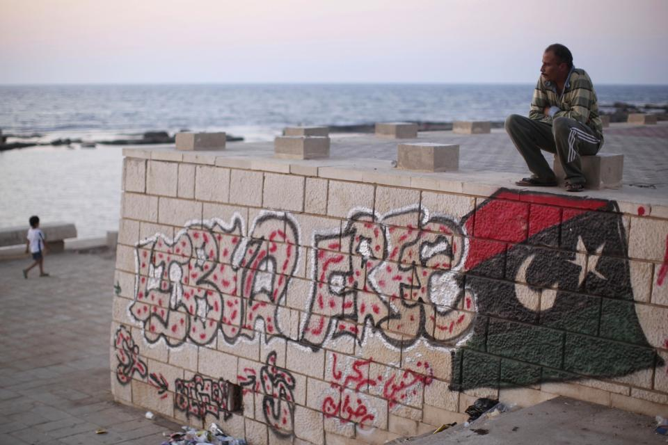 "Painter Rafat Askar, 46, rests at the seaside of the rebel-held town of Benghazi, Libya, Thursday, Aug. 18, 2011. The paint on the wall reads: ""Libya Free."" (AP Photo/Alexandre Meneghini)"