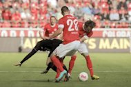 FC Augsburg's midfielder Marcel de Jong (L) clashes with Mainz' striker Adam Szalai (C) and midfielder Nicolai Mueller during their first division German Bundesliga football match in Mainz, western Germany. Mainz claimed their first win of the season, beating Augsburg 2-0