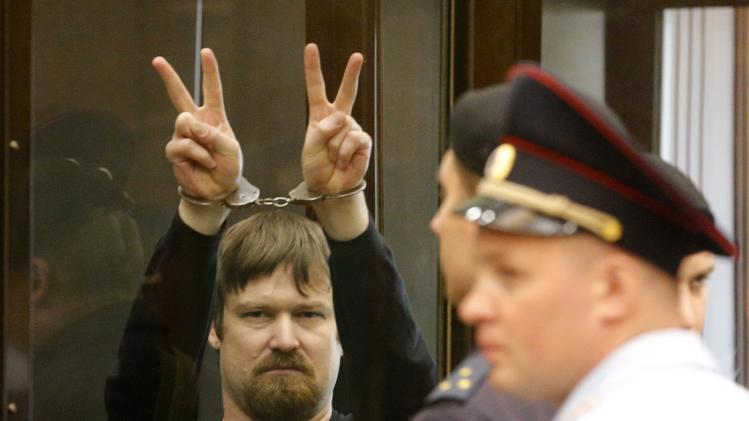 Razvozhayev, co-defendant of opposition leader Udaltsov, gestures from defendants cage during a court hearing in Moscow