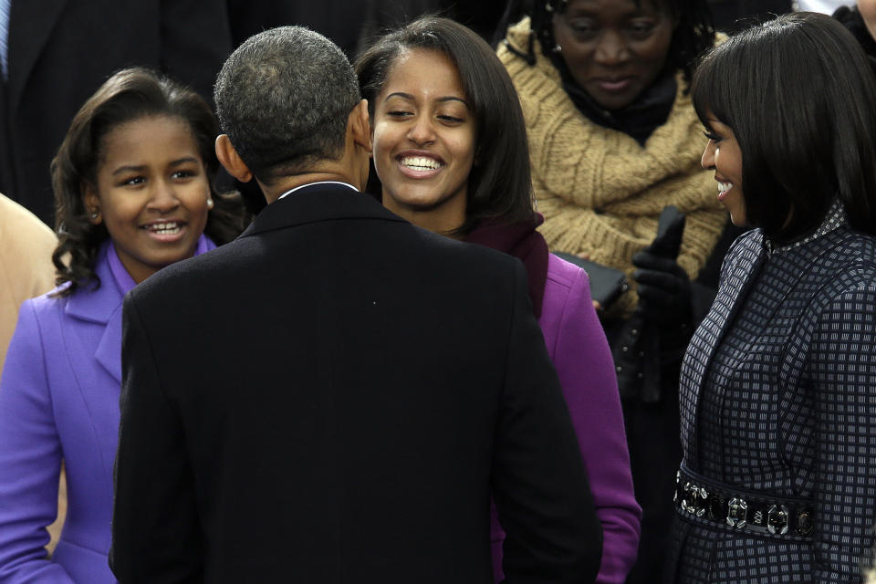 President Barack Obama greets his daughter Sasha and Malia as first lady Michelle Obama watches at the ceremonial swearing-in at the U.S. Capitol during the 57th Presidential Inauguration in Washington, Monday, Jan. 21, 2013. (AP Photo/Evan Vucci)