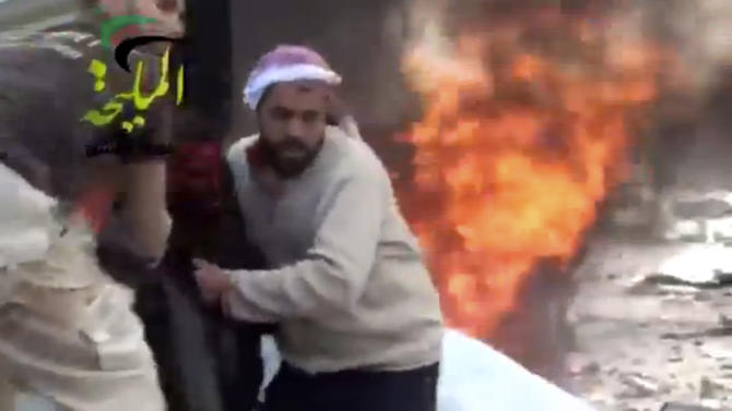 This citizen journalism image taken from video provided by Shaam News Network, which has been authenticated based on its contents and other AP reporting, shows a wounded man being pulled from the site of a Syrian government airstrike on a gas station in the eastern Damascus suburb of Mleiha, Syria, Wednesday, Jan. 2, 2013. Activists say dozens of people have been killed or wounded in an air raid on a gas station near the capital Damascus. (AP Photo/Shaam News Network via AP video)