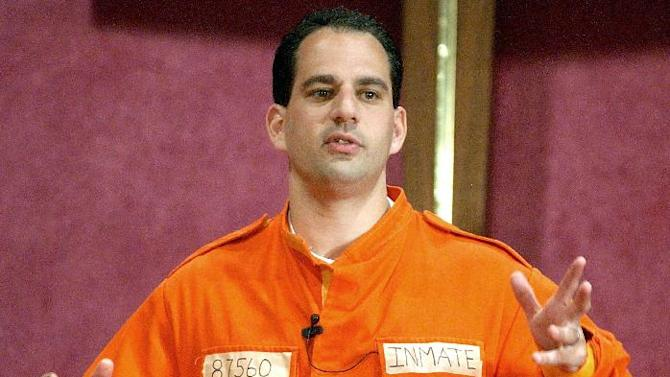 FILE - In this July 7, 2002 file photo, Barry Minkow, a convicted con artist and the co-founder of the for-profit Fraud Discovery Institute, wears a prison jumpsuit costume as he delivers a sermon on materialism at the Community Bible Church in San Diego. Minkow, who went from teenage millionaire to convicted con artist to professional fraud fighter and pastor, was convicted Wednesday, Jan. 22, 2014 of cheating his San Diego church congregation out of some $3 million. (AP Photo/Denis Poroy, File)