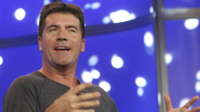 """FILE - American Idol"""" judge Simon Cowell  speaks during the 2007 Fox Winter Press Tour in this January 20 2007, file photo in Pasadena, Calif. British Police say 29-year old woman, Leanne Zaloumis has been charged with breaking into Cowell's house by smashing a window with a brick late Saturday March 24, 2012, but was detained by Cowell's security team before reaching the entertainment mogul who was at home at the time.  Zaloumis is to appear in court Monday March 26, 2012. (AP Photo/Rene Macura, File)"""