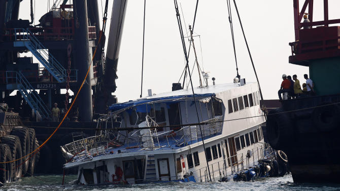 A half submerged boat is lifted by cranes Tuesday Oct. 2, 2012 after Monday night's collision near Lamma Island, off the southwestern coast of Hong Kong Island. The boat packed with revelers on a long holiday weekend collided with a ferry and sank, killing at least 36 people and injuring dozens, authorities said.  (AP Photo/Vincent Yu)