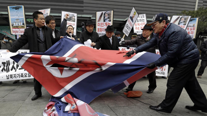 """South Korean protesters slit up a North Korean flag during an anti-North Korea rally in Seoul, South Korea, following a nuclear test conducted by North Korea Tuesday, Feb. 12, 2013. North Korea said it successfully detonated a miniaturized nuclear device at a northeastern test site Tuesday, defying U.N. Security Council orders to shut down atomic activity or face more sanctions and international isolation. The signs read """" Out, Kim Jong Un."""" (AP Photo/Lee Jin-man)"""