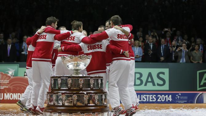 Switzerland's team members celebrate alongside the Davis Cup trophy after winning the Davis Cup tennis tournament final match against France at the Pierre-Mauroy stadium in Villeneuve d'Ascq
